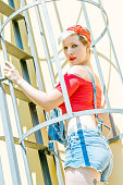 Young blonde pinup girl with a red bow on a emergency stairway. Concept pinup woman.