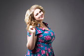 Young beautiful blonde plus size model in dres, xxl woman portrait on gray studio background, makeup and hairstyle