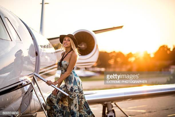 Young blonde woman entering private jet airplane