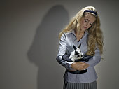 Young Blonde Woman Holding Rabbit in Top Hat