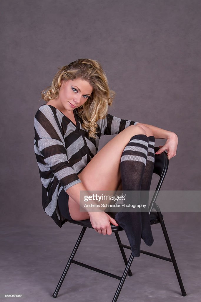 Young blonde woman in striped outfit on a chair : Stock Photo