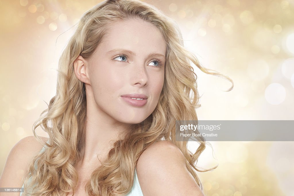 young blonde woman looking toward the sun : Stock Photo