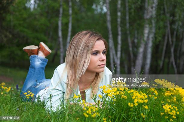Young blonde woman lying down in the grass