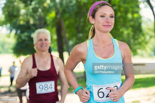 Young blonde woman running in marathon or 5k race
