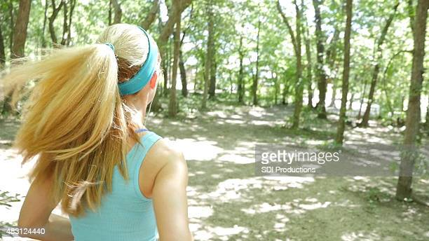 Young blonde woman running off road on dirt path