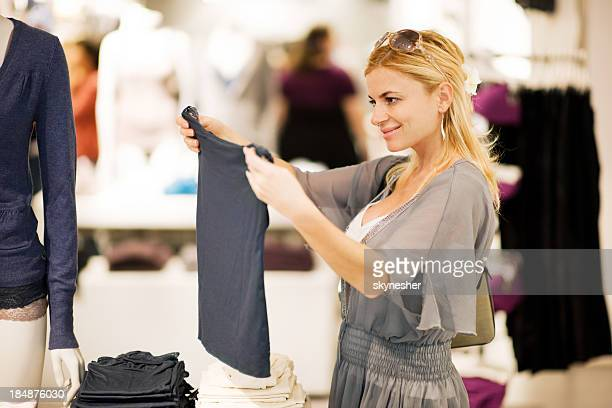 Young blonde woman shopping for clothes.