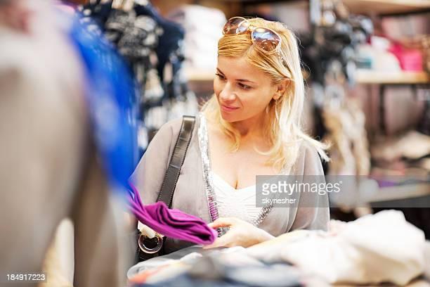 Jeune blonde femme shopping pour les vêtements