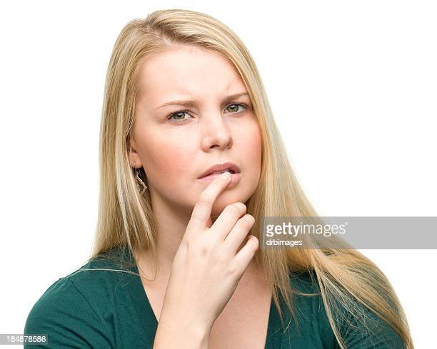 A young blonde woman thinking with her finger on lip