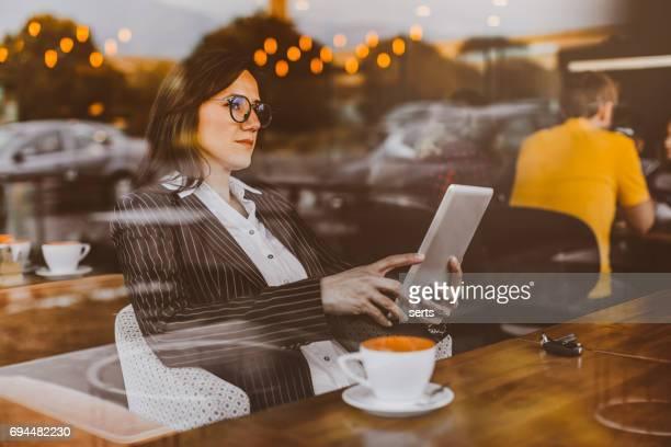 Jeune femme blonde avec tablette en café-restaurant