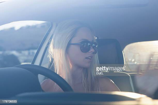 Young blonde women in car wearing sunglasses