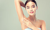 Gorgeous, young, blue-eyed woman  is touching the clean, soft skin of own armpit. Pure woman's beauty. Facial and skin treatment, cosmetology, beauty technologies and armpit epilation.