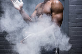 Young Bodybuilder shaking Chalk off his hands in the  gym