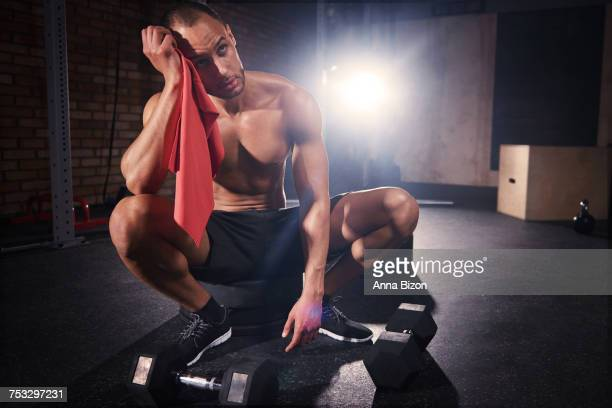 Young bodybuilder wiping sweat with a towel. Mielec, Poland