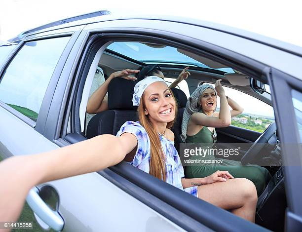 Young boho tourists traveling by car and making selfie