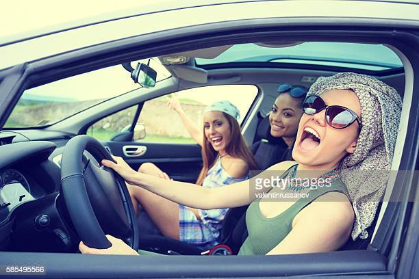 Young boho women traveling and listening music in the car