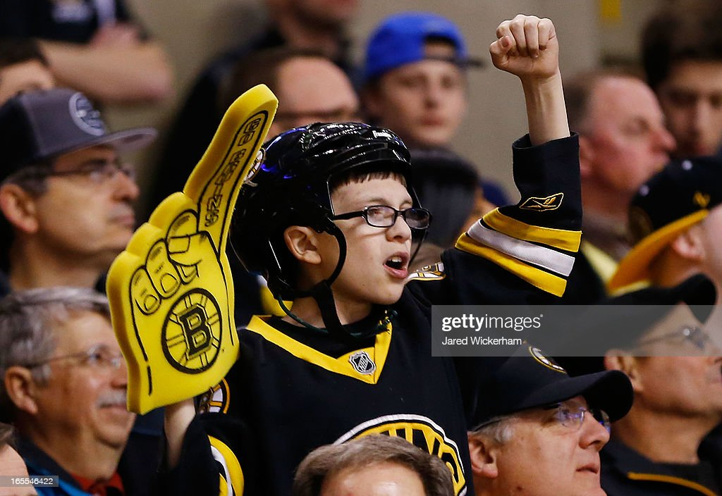 A young Boston Bruins fan cheers on his team from the stands during the game against the New Jersey Devils on April 2, 2013 at TD Garden in Boston, Massachusetts.