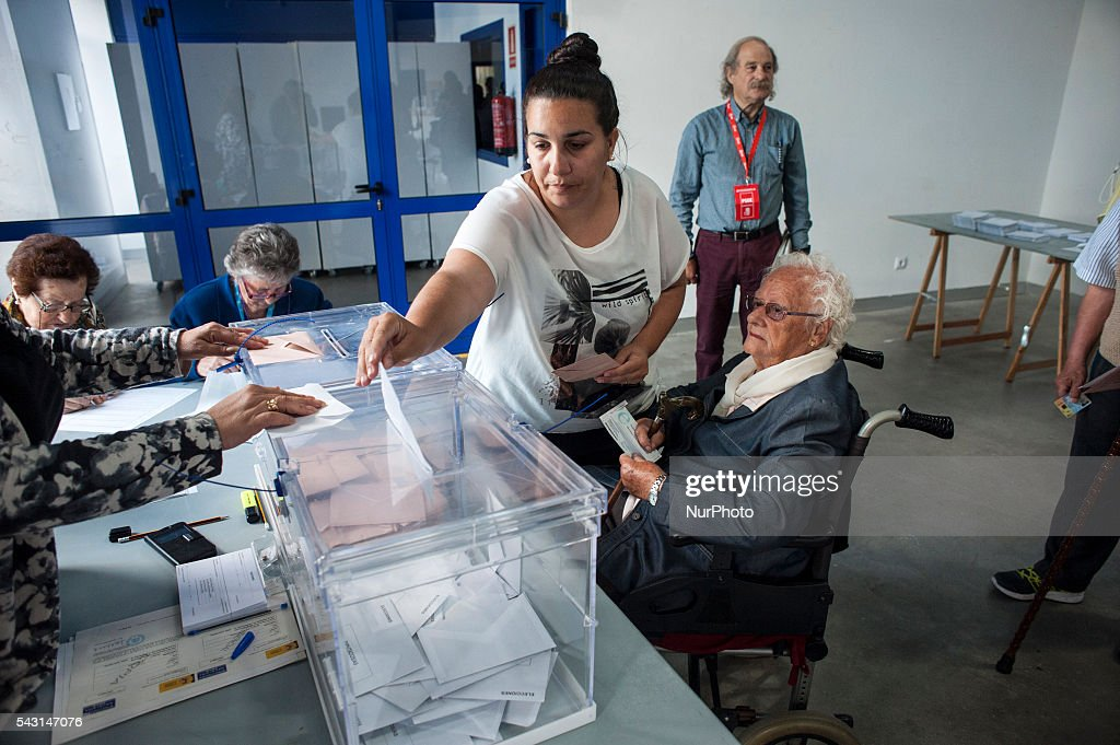 A young bounce helps a woman in a wheelchair at a polling station during the general elections on June 26 in Spain . Spanish voters head back to the polls after the last election in December failed to produce a government. Latest opinion polls suggest the Unidos Podemos left-wing alliance could make enough gains to come in second behind the ruling center right Popular Party.