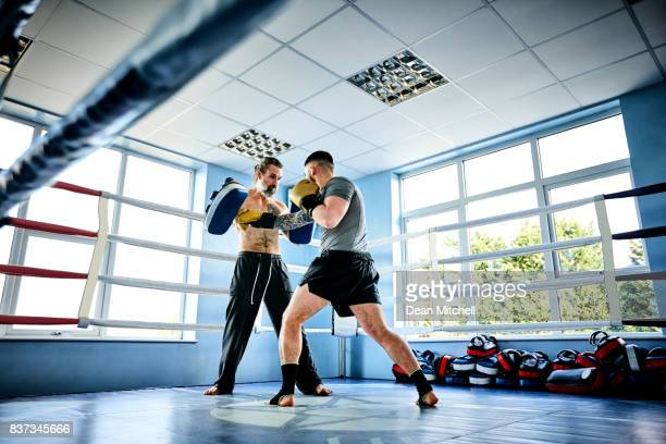 Young boxer practicing with his coach at gym