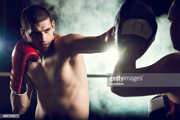 Joven boxeador practicar con su entrenador.