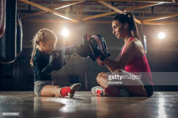 Young boxing coach practicing with small girl in a gym.
