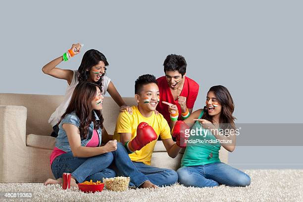 Young boxing fans cheering for friend in living room