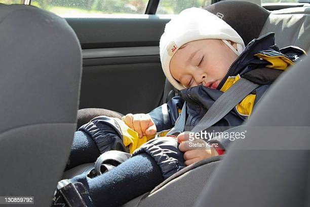 Young boy, 18 months, sleeping in a car seat