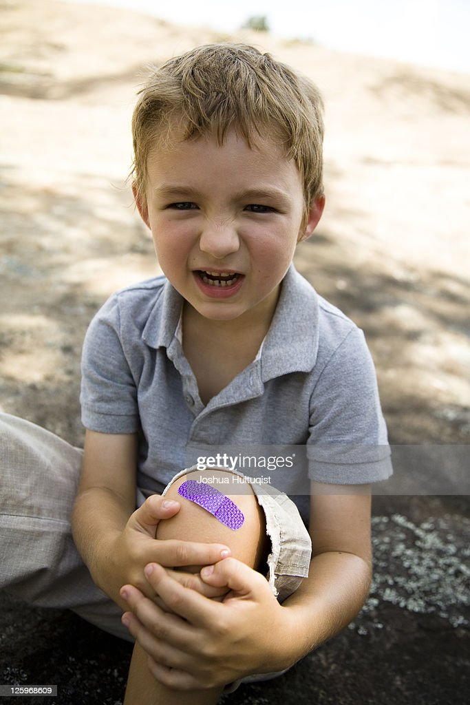 Young boy, 5 years old, holding hurt knee with purple band-aid on knee : Stock Photo