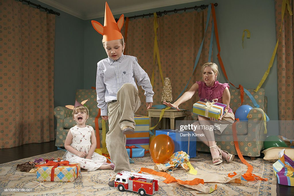 Young boy (6-7) about to destroy toy car, girl (3-4) crying, mother sitting in armchair