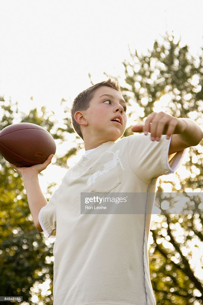 Young boy about to pass a football : Stock Photo