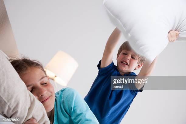 Jeune garçon sur se réveiller sa sœur d'oreiller