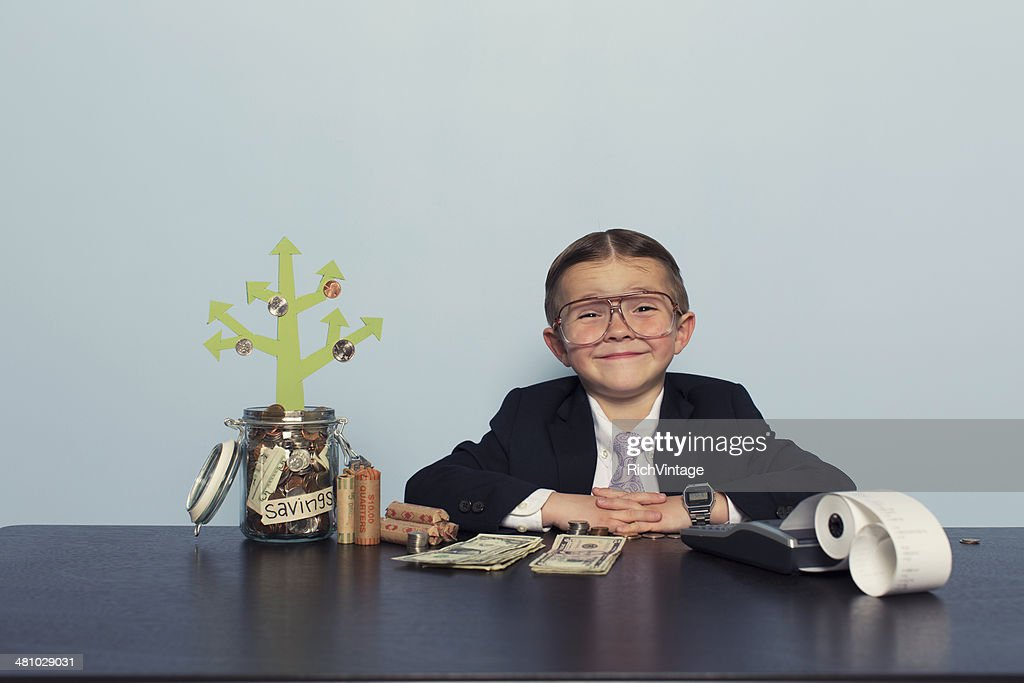 Young Boy Accountant Grows Money in Savings Account : Stock Photo