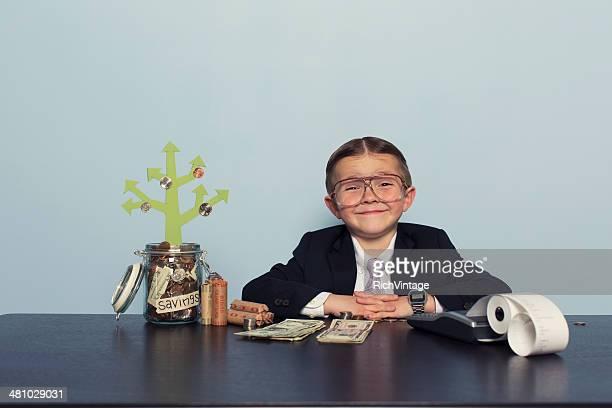 Jeune garçon comptable de faire de l'argent dans un compte d'épargne
