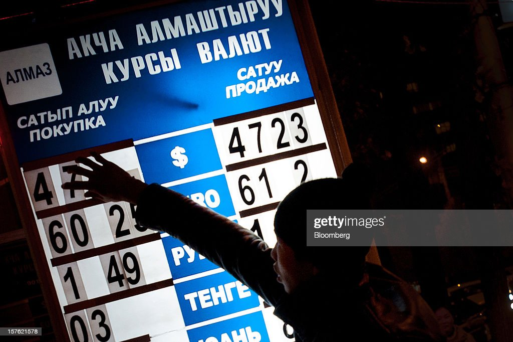 A young boy adjusts number tiles displaying the exchange rate on a currency exchange board at night in Bishkek, Kyrgyzstan, on Wednesday, Nov. 7, 2012. Landlocked Kyrgyzstan is the only country in the world that hosts both Russian and U.S. military bases. Photographer: Noriko Hayashi/Bloomberg via Getty Images
