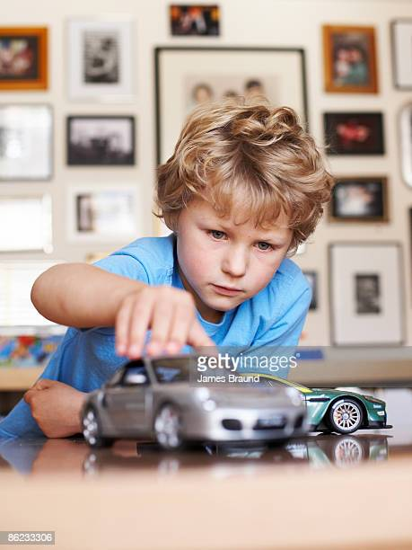 Young boy aged five playing with toy cars