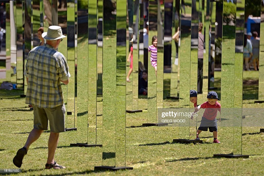 A young boy (below-R) and a man (L) enjoy a maze of mirrors that make up the installation 'Field' from Art & About Sydney on September 23, 2013. Field, developed by New Zealand architecture collective 'Out of the Dark', is a mesmerising set of mirrors on 81 posts designed to be a place of literal reflection where the perspective is ever-changing, encouraging curious passers-by. AFP PHOTO / Greg WOOD