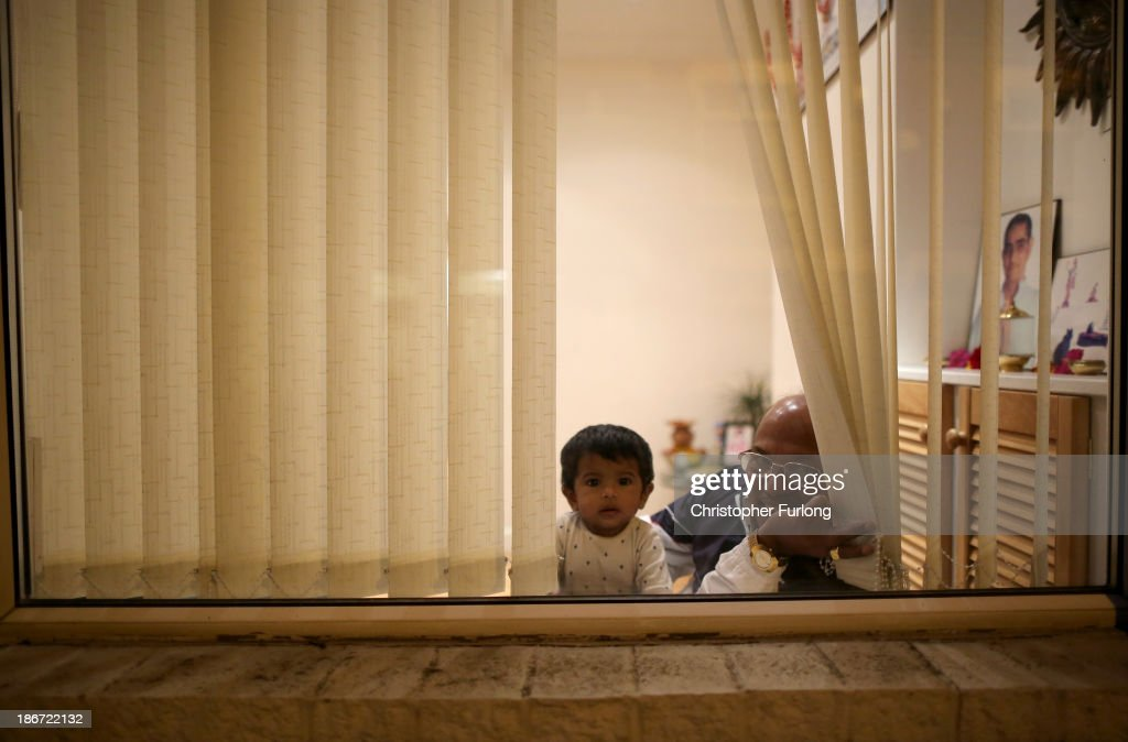A young boy and a man look out of the window to watch people celebrate the Hindu festival of Diwali on November 3, 2013 in Leicester, United Kingdom. Up to 35,000 people attended the Diwali festival of light in Leicester's Golden Mile in the heart of the city's Asian community. The festival is an opportunity for Hindus to honour Lakshmi, the goddess of wealth and other gods. Leicester's celebrations are one of the biggest in the world outside India.