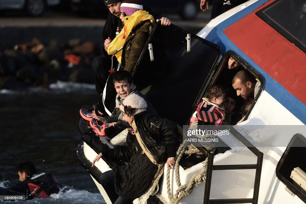 A young boy and a woman cry out for help with other refugees and migrants as their boat sinks off the Greek island of Lesbos island while crossing...