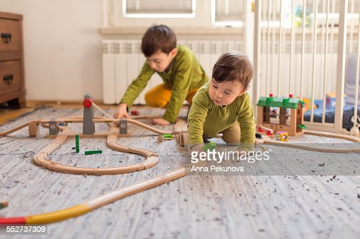 Young boy and baby boy playing indoors