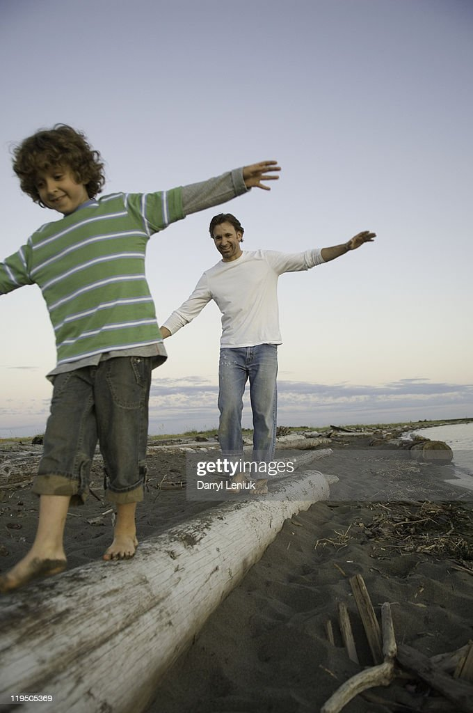 young boy and father balancing on log at beach : Stock Photo