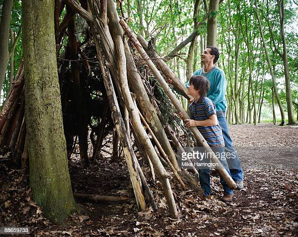 Young boy and father in forest.