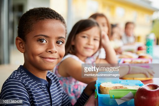 Young boy and girl at school lunch table smiling to camera : Stock Photo