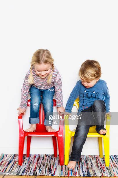 Young boy and girl , crouching on colourful chairs