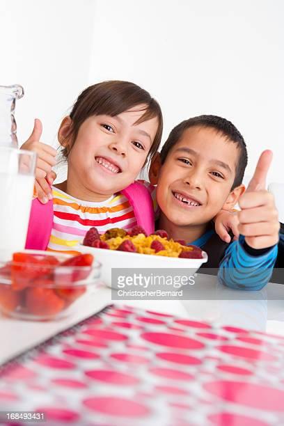 Jeune Garçon et fille appréciant leur petit-déjeuner avant de l'école