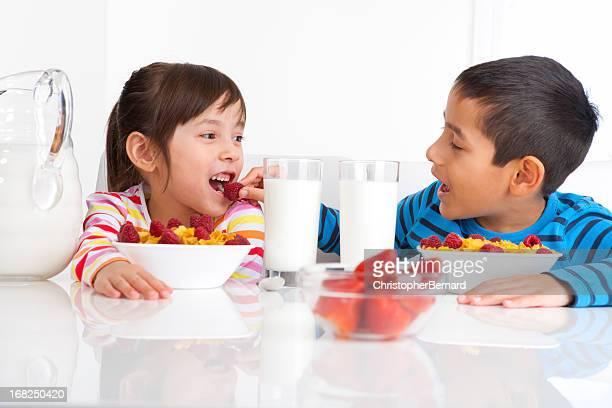 Jeune Garçon et fille appréciant leur petit-déjeuner