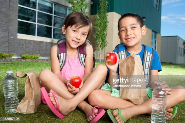 Young boy and girl having a snack outside of school