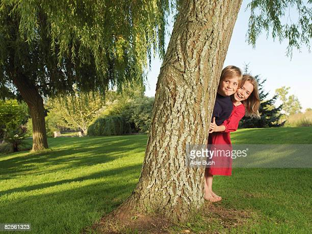 Young boy and girl hiding behind tree