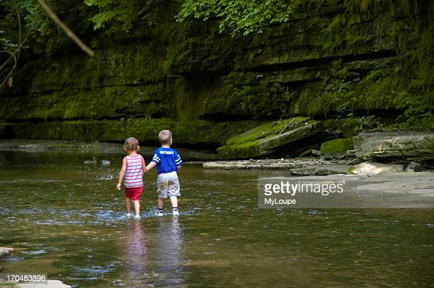 Young boy and girl holding hands and wading in a creek