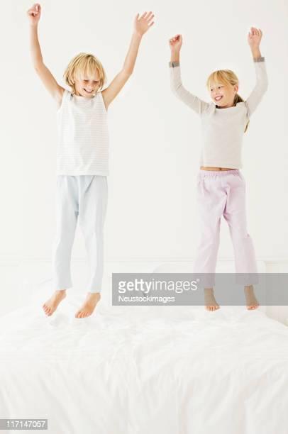 Young Boy and Girl salto en la cama