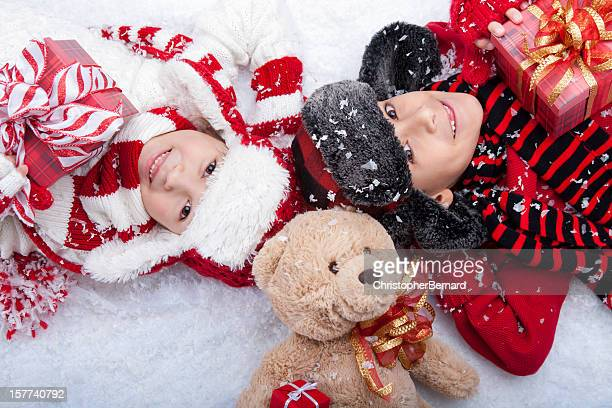 Young boy and girl laying with their bear