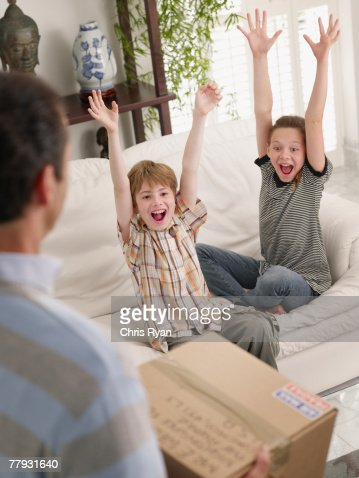Young boy and girl on a sofa cheering with man in foreground : Stock Photo